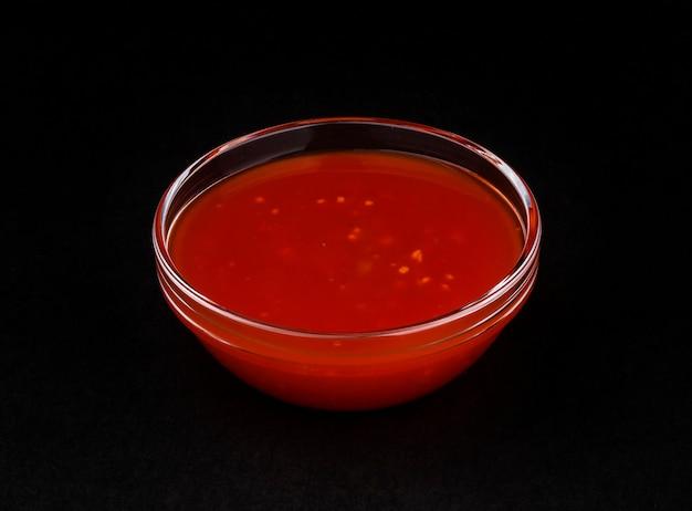 Острый соус чили, изолированный на черном