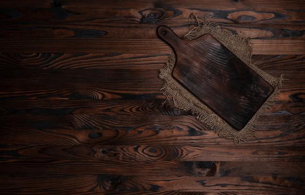 茶色の木の黄麻布ナプキンとまな板、トップビュー