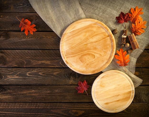 暗い木製のテーブル、ピザの葉と秋の背景に丸いまな板