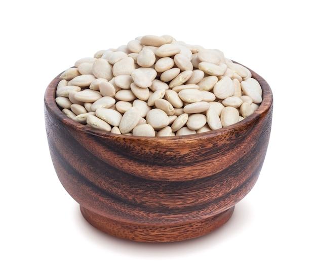 Белая фасоль в деревянной миске на белом фоне