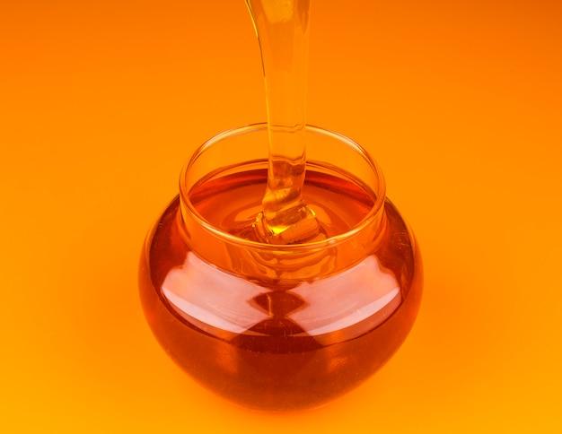 ガラスの瓶に蜂蜜を注ぐ