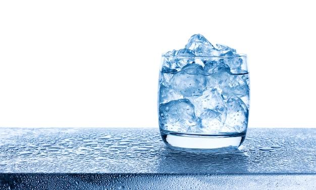 白い背景の上のガラスに砕いたアイスキューブと水します。