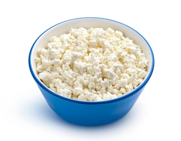 白で隔離される青いボウルのカッテージチーズ