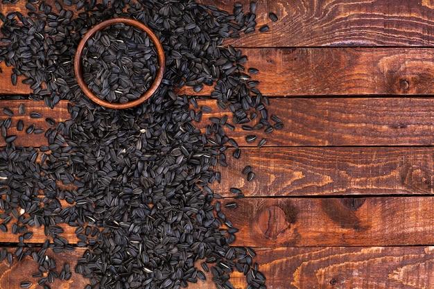 木製の背景に黒いヒマワリの種