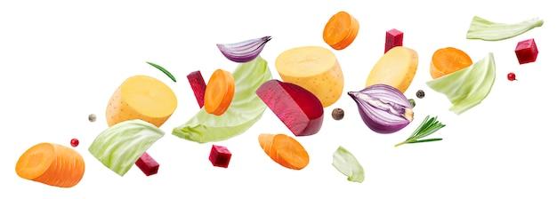 白で隔離されるさまざまな野菜の落下片