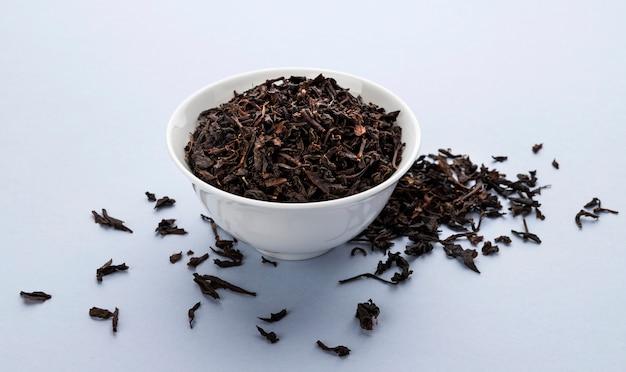 Сухие листья черного чая, изолированные на белом