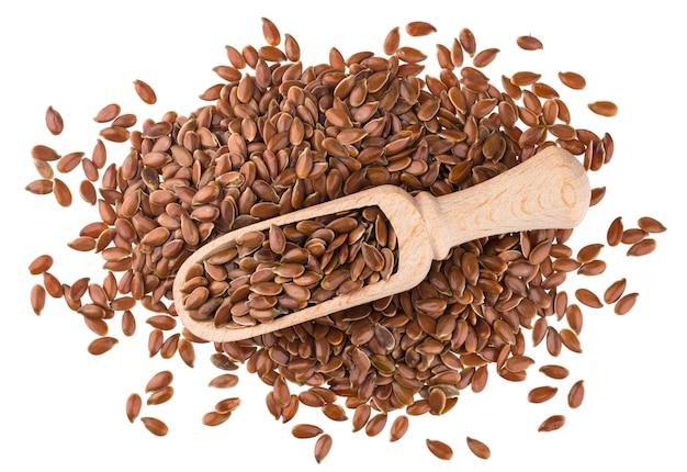 Семена льна в деревянный ковш на белом фоне