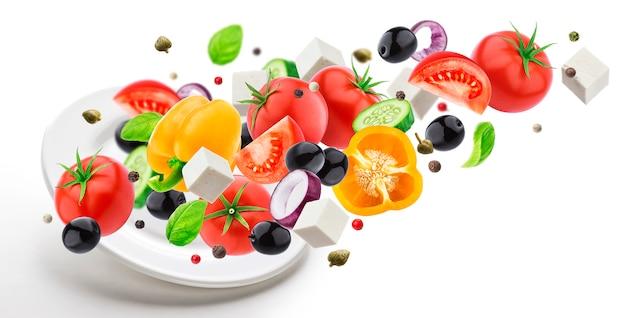 Тарелка с падающим греческим салатом на белом фоне