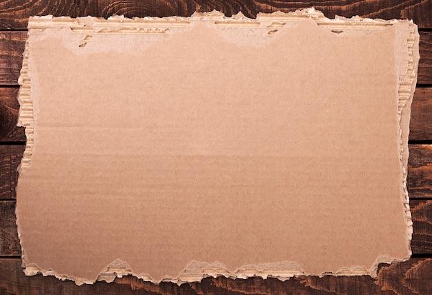 破れた紙。木製のテクスチャに引き裂かれた段ボール。