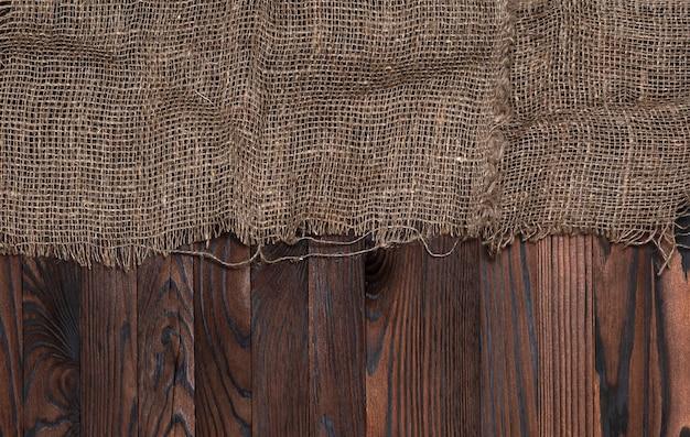 茶色の木製の背景、トップビューで古い黄麻布のナプキン