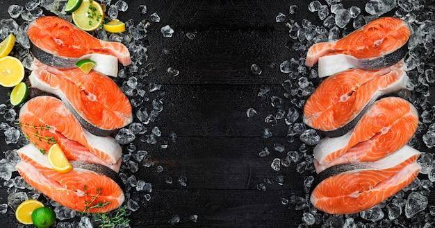 黒の背景に、氷の上の新鮮なサーモンステーキ。