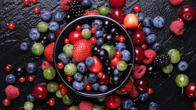 黒い木製のトップビューで新鮮な野生の果実のコレクション