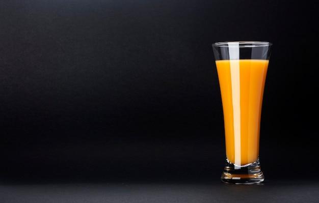 テキスト、新鮮な柑橘系のカクテルのためのコピースペースと黒に分離されたオレンジジュースのガラス