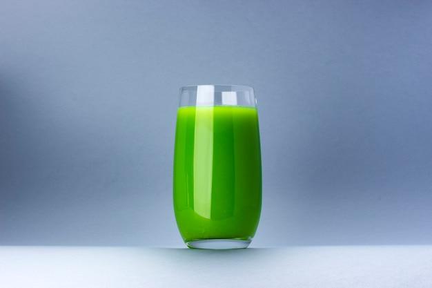 Стакан зеленого сока на белом фоне с копией пространства для текста