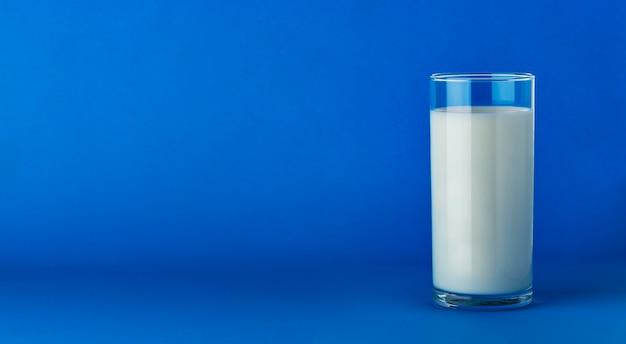 コピースペースを持つ青に分離されたミルクのガラス