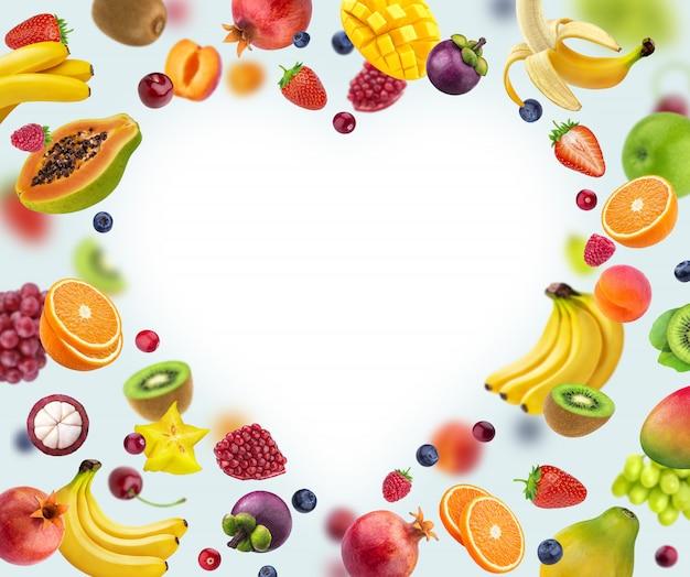 白で隔離され、さまざまな果物や果実から成っているハート形フレーム