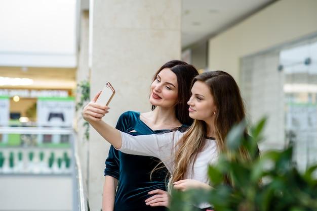 店で自分撮りをしている二人の女の子。