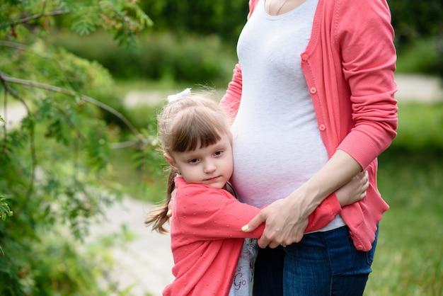 妊娠中の母親を抱き締める少女