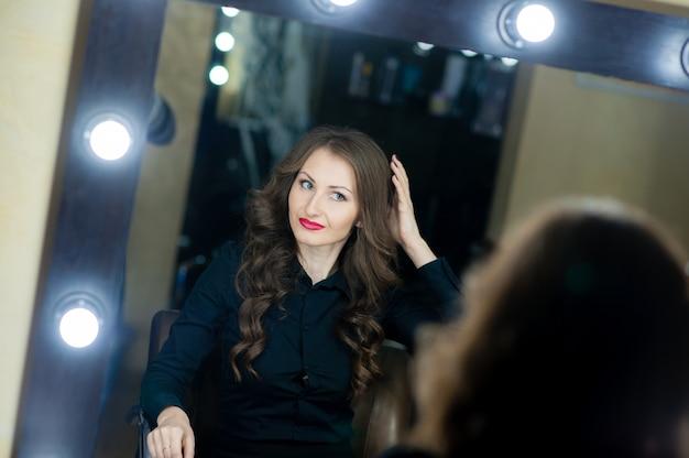 鏡の近くの美しい少女メイクアップアーティスト