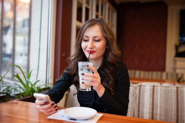 Красивая девушка пьет кофе и смотрит в телефон
