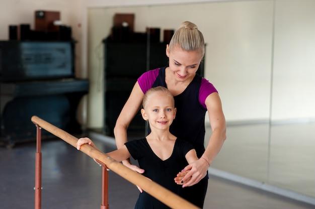 振付師は子供にバレエの位置を教えます