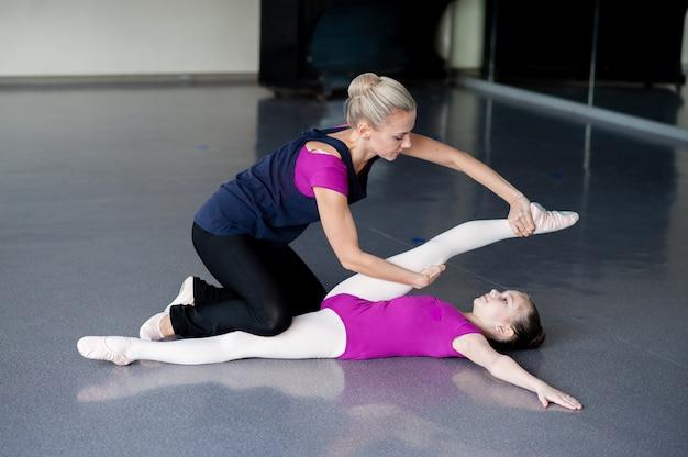 Обучение здоровому образу жизни на примере - женщина и маленькая девочка тренируются вместе