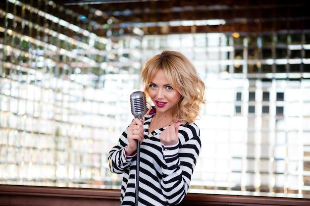 美しい女性、ブロンド、マイク。歌う、美しい笑顔