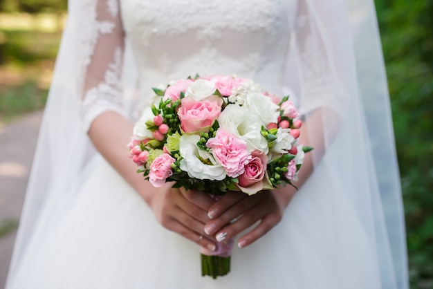 花嫁はウェディングブーケを保持しています。