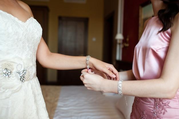 花嫁はブレスレットを着ています。