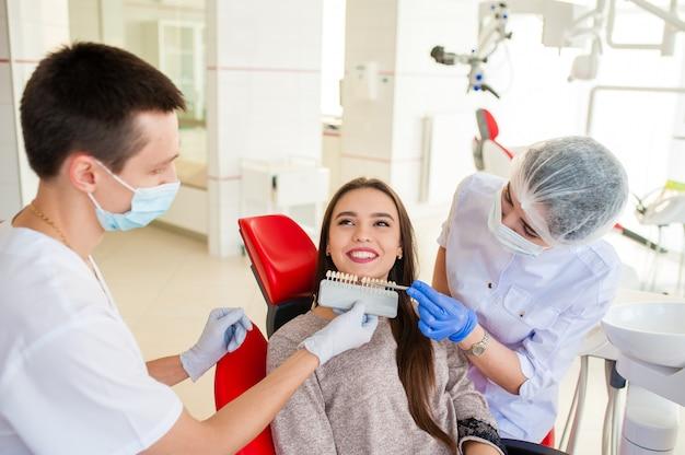 助手の歯科医は、美しい少女に歯の色を拾います。