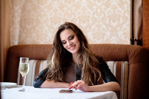 レストランのテーブルで電話で美しい少女。