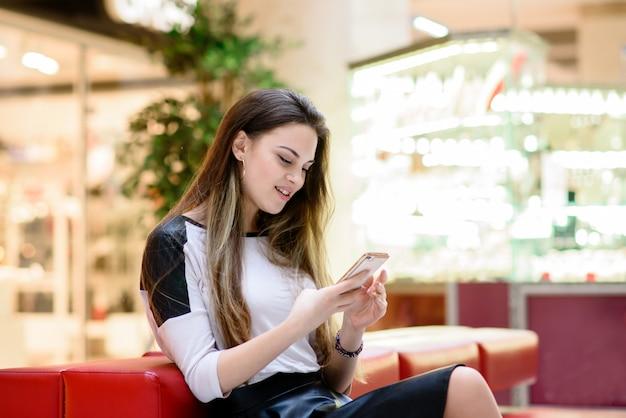 Красивая девушка поднимает сообщение на телефоне.