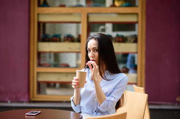 路上で美しい少女コーヒーを飲む人。