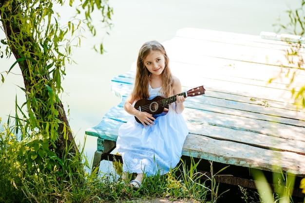 Портрет милой девушки, сидящей на улице с укулеле