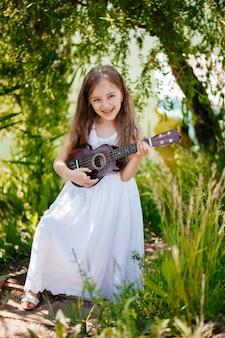 女の子は草の上に立って、ヘッドフォンを着用し、ウクレレ弦を弾くことを学んでいます。自然公園で学校の外で学んでいます。