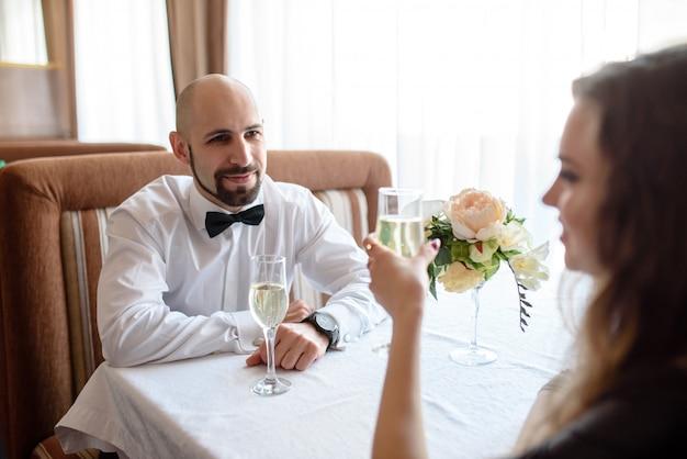 レストランでシャンパンを祝って、飲む美しいカップル。