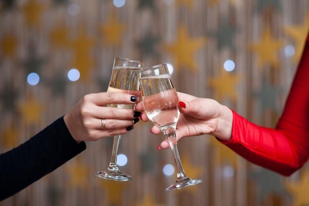 お祝い。乾杯のシャンパンのグラスを持っている人