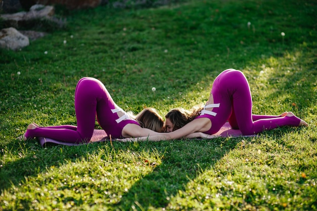 木々を通って来る柔らかい太陽フレアと紫のマットの上の公園でヨガのポーズを実行するタイトなアクティブな摩耗を着て美しいブルネットの女性