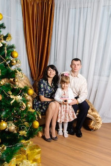 ママ、パパと娘がクリスマスツリーでポーズ