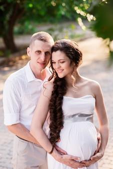 幸せな妊娠中のカップルは自然の中を歩きます。