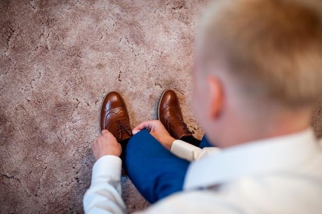 Человек застегивает свою элегантную обувь