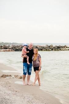 Молодая семья с сыном гуляет по морю