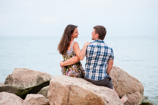 海の岩の上の若いカップル