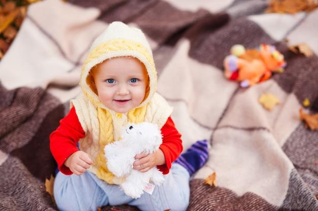 少女は笑顔で秋の公園で遊んでいます。
