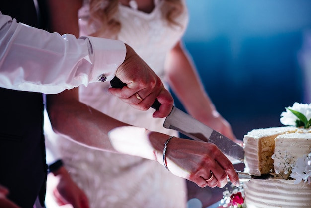 カップルの手がウェディングケーキ、花嫁と結婚式を切る