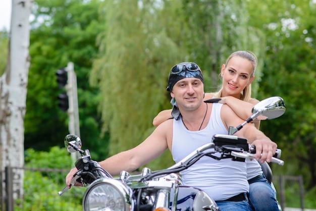愛の美しいカップルはバイクに乗っています。