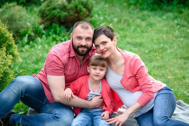 Счастливая семья гуляя в парк беременность.