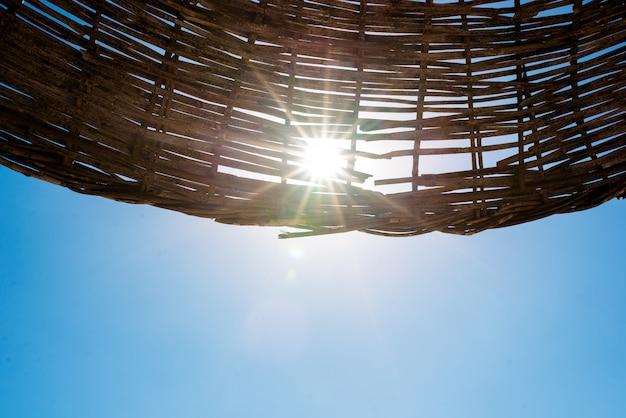 太陽は浜辺の傘を通して輝いています。