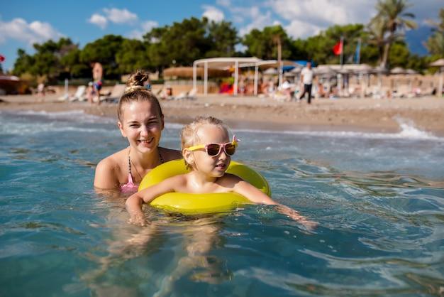 Мать и маленькая дочь купаются в море.
