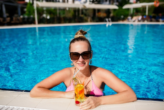 美しい少女はプールでカクテルを飲んでいます。